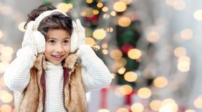Glückliche tragende Ohrenschützer des kleinen Mädchens am Weihnachten Stockfoto