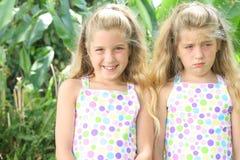 Glückliche traurige Doppelschwester lizenzfreies stockbild
