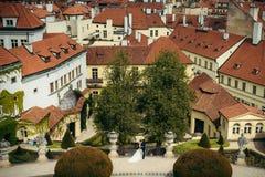 Glückliche umarmende Jungvermähltenpaare am Hintergrund der Altbauten von Prag lizenzfreies stockbild