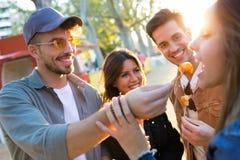 Glückliche und attraktive junge Gruppe Freunde, die Schnellimbiß essen essen und teilen herein, Markt in der Straße lizenzfreie stockfotografie