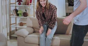 Glückliche und aufgeregte Paare haben einen stark tragenden Tag in einem neuen Haus, nachdem sie entspannend auf dem Sofa und dem stock video footage