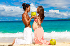 Glückliche und der Junge schwangere Paare mit den Kokosnüssen, die Spaß auf einem tr haben Stockfotografie