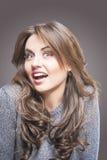 Glückliche und frech junge Frau in Gray Sweater auf Grey Backgroun Stockbild