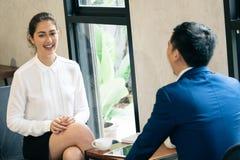 Glückliche und lächelnde Geschäftsberufstätige frau in der Diskussion mit anderem männlichem Geschäftsmannpartner im Team im Konf lizenzfreies stockbild