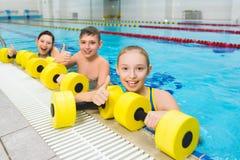 Glückliche und lächelnde Gruppe Kinder, die Übungen in einem Swimmingpool tun stockfotografie