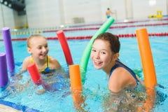 Glückliche und lächelnde Gruppe Kinder, die lernen, mit Poolnudel zu schwimmen Lizenzfreie Stockfotos