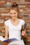 Glückliche und lächelnde Jugendliche mit großem Notizblock Stockfoto