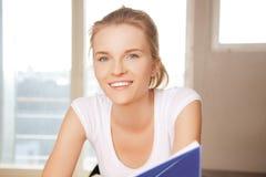 Glückliche und lächelnde Jugendliche mit großem Notizblock Lizenzfreies Stockbild