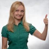 Glückliche und lächelnde junge Frau im zufälligen grünen Hemd, das gerade Kamera mit dem Daumen oben untersucht lizenzfreies stockfoto