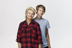 Glückliche und lächelnde Mutter und Sohn Liebevolles Familienporträt gegen weißen Hintergrund stockbild