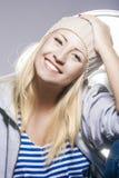 Glückliche und positive junge kaukasische blonde Frau gegen Studio E Stockbild