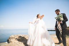 Glückliche und romantische Szene gerade von den verheirateten jungen Hochzeitspaaren, die auf schönem Strand aufwerfen lizenzfreie stockfotos