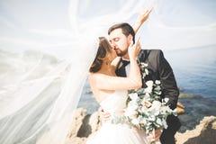 Glückliche und romantische Szene gerade von den verheirateten jungen Hochzeitspaaren, die auf schönem Strand aufwerfen stockfotografie