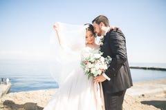 Glückliche und romantische Szene gerade von den verheirateten jungen Hochzeitspaaren, die auf schönem Strand aufwerfen lizenzfreies stockbild