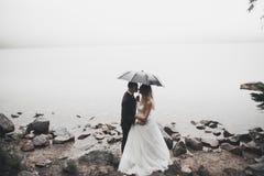 Glückliche und romantische Szene gerade von den verheirateten jungen Hochzeitspaaren, die auf schönem Strand aufwerfen stockfoto