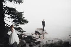 Glückliche und romantische Szene gerade von den verheirateten jungen Hochzeitspaaren, die auf schönem Strand aufwerfen lizenzfreie stockfotografie
