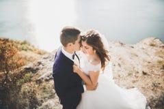 Glückliche und romantische Szene gerade von den verheirateten jungen Hochzeitspaaren, die auf schönem Strand aufwerfen stockbild