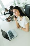Glückliche und schöne junge Geschäftsfrau, die an einem Bürovorsprung sitzt Stockbild