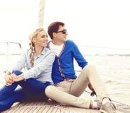 Glückliche und schöne junge Paare, die auf Plattform sitzen und ein Gehung haben Stockbild