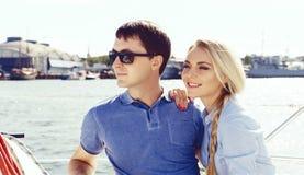 Glückliche und schöne junge Paare, die einen Rest auf einer Yacht haben Trave Lizenzfreie Stockbilder