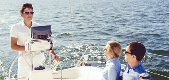 Glückliche und schöne Paare, die einen Rest auf Yacht haben und c aufpassen Lizenzfreies Stockbild