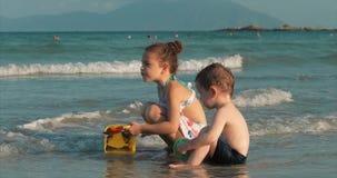 Glückliche und sorglose Kinder, die durch das Meer mit Sand spielen Kinderspielen, Bruder- und Schwesterspiel durch das Meer gl?c stock video