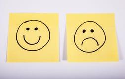 Glückliche und traurige Gesichter auf Notiz-Papier Lizenzfreies Stockbild