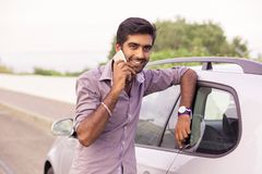 Glückliche Unterhaltung des Mannes am Telefon, das auf der Tür seines Autos sich lehnt lizenzfreies stockfoto