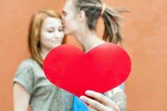 Glückliche Valentinsgruß-Tagespaare, die rotes Herzsymbol halten Stockfotografie