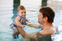 Glückliche Vaterschwimmen von mittlerem Alter mit netter entzückender Babytochter im Rauschpool Lächelnder Vati und kleines Kind, lizenzfreies stockbild