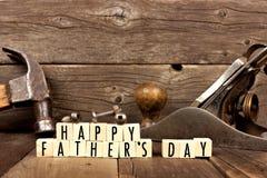 Glückliche Vatertagsblöcke mit Werkzeugen im Hintergrund gegen Holz stockbild
