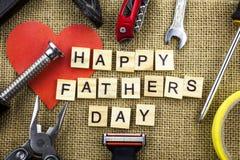 Glückliche Vatertagsmitteilung auf einem Jutefaserhintergrund des groben Sackzeugs mit Rahmen von Werkzeugen und von Bindungen stockfotografie