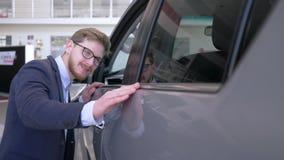 Glückliche Verbrauchermänner in Brillen mit dem Vergnügen, das neues Automobil leicht lächelnd an der Verkaufsstelle streicht stock video