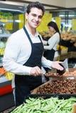 Glückliche Verkäufer mit Kastanien Stockfotografie