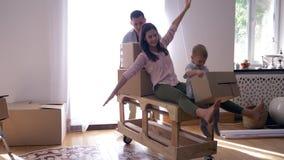 Glückliche Verlegung, junger Mann trägt Frau mit kleinem Sohn auf Tabelle in der neuen Wohnung mit Kästen mit Sachen stock video