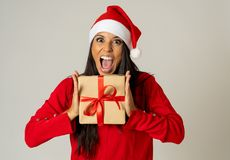 Glückliche verrückte aufgeregte junge Frau in Weihnachtsmann-Hut mit Weihnachtsgeschenk lachend und lächelnd stockbild