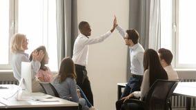 Glückliche verschiedene Angestellte, die hohen zusammen feiernden geteilten Gewinn fünf geben stockbilder