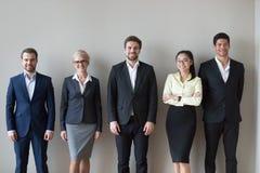 Glückliche verschiedene Führungskräfteteamstellung nahe Wand Headshotporträt stockfotografie