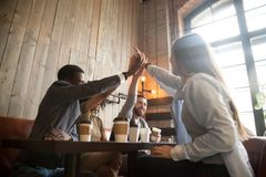 Glückliche verschiedene Freunde, die das Hoch fünf kühlt heraus im Café geben stockfotografie