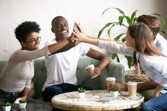 Glückliche verschiedene Freunde, die zusammen hohe fünf im Café geben lizenzfreies stockbild