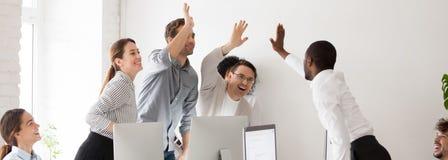 Glückliche verschiedene tausendjährige Workmates, die hoch fünf feiernden Unternehmenserfolg geben lizenzfreie stockfotos