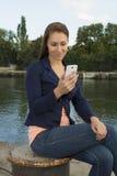 Glückliche Versenden von SMS-Nachrichten der jungen Frau Lizenzfreie Stockbilder
