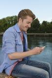 Glückliche Versenden von SMS-Nachrichten des jungen Mannes Stockfoto