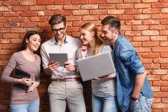 Glückliche vier Freunde, die moderne Geräte verwenden lizenzfreie stockfotos
