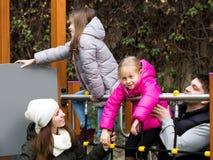 Glückliche vierköpfige Familie am children& x27; s-Spielplatz Lizenzfreie Stockfotografie