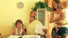 Glückliche vierköpfige Familie, die Dokumente unterzeichnet stock footage