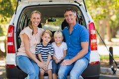 Glückliche vierköpfige Familie, die im Autokofferraum sitzt Stockfotografie