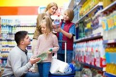 Glückliche vierköpfige Familie, die Mineralwasser kauft Lizenzfreie Stockfotos