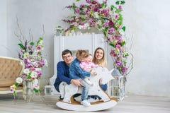 Glückliche vierköpfige Familie sitzen im Raum mit Blumen und im Spiel mit Kindern auf ihrem hölzernen Spielzeugpferd Stockfoto