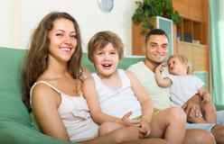 Glückliche vierköpfige Familie zu Hause Stockbild